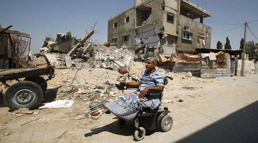 Palestinian maths teacher Ali Wahdan moves his motorised wheelchair past the ruins of his house, that witnesses said was destroyed by Israeli shelling during a 50-day war last summer, in Beit Hanoun town, in the northern Gaza Strip July 6, 2015. © Suhaib Salem