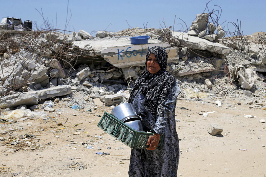 A Palestinian woman walks past the remains of a house, that witnesses said was destroyed by Israeli shelling during a 50-day war last summer, in Khan Younis in the southern Gaza Strip June 29, 2015. Picture taken June 29, 2015. © Ibraheem Abu Mustafa