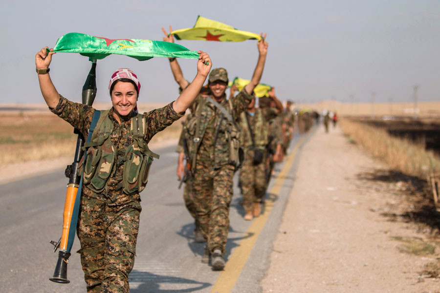 Kurdish fighters gesture while carrying their parties' flags in Tel Abyad of Raqqa governorate after they said they took control of the area June 15, 2015. © Rodi Said