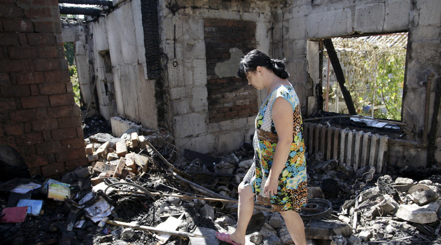 A woman walks amidst the debris of a damaged residential building, which according to locals was caused by recent shelling, in Donetsk, Ukraine August 2, 2015. © Alexander Ermochenko