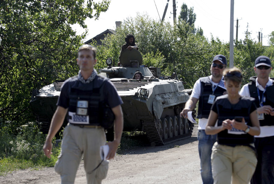 Members of the Organisation for Security and Co-operation in Europe (OSCE) walk past an armoured personnel carrier (APC) of the self-proclaimed Donetsk People's Republic forces outside the village of Novolaspa in Donetsk region, Ukraine, July 19, 2015. © Alexander Ermochenko