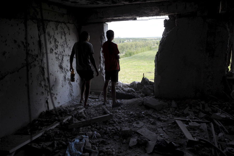 Local residents look through a hole in a damaged multi-storey building, which according to locals was caused by recent shelling, in Avdiivka in Donetsk region, Ukraine, July 18, 2015. © Maksim Levin