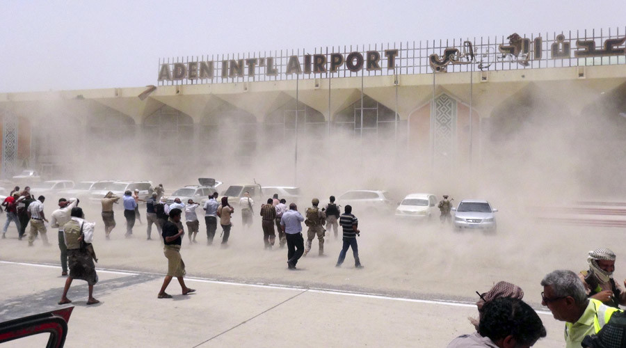 People seek cover from rising dust as a Qatari military cargo plane carrying aid lands at the international airport of Yemen's southern port city of Aden August 1, 2015. © Stringer