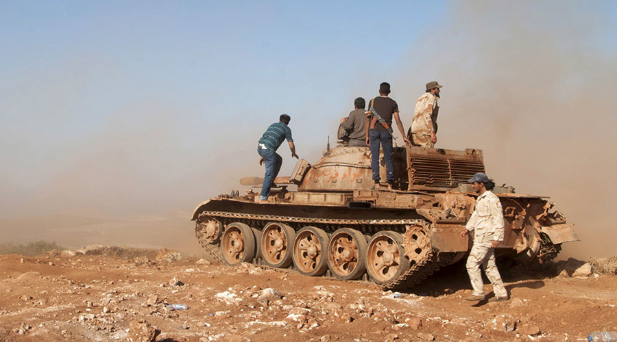Members of the Libyan pro-government forces stand on a tank during their deployment in the Lamluda area, southwest of the city of Derna, Libya, June 16, 2015. © Stringer