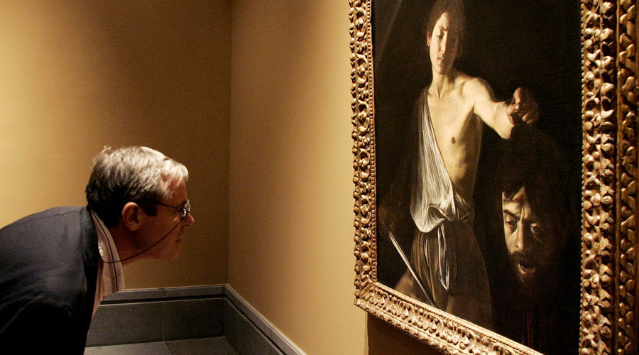 "A man studies ""David with the head of Goliath"" by Italian painter Caravaggio at an exhibition in Naples, 23 October 2004. ©  Mario Laporta"