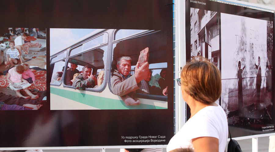 A woman in Novi Sad, Serbia, looks at a photo of a refugee column pelted by rocks in Croatia during August 1995's 'Operation Storm'
