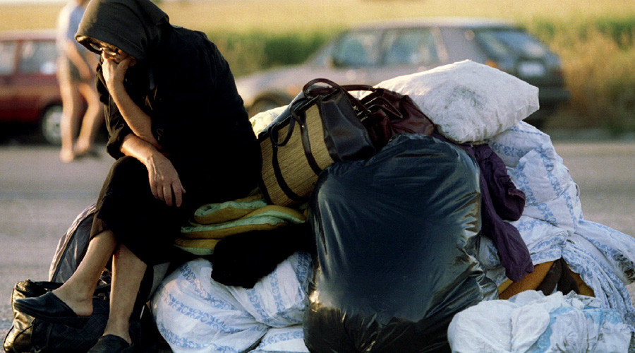 A Serb refugee from Krajina rests by her belongings August 13, 1995, on the main motorway near the Yugoslav capital. © Yannis Behrakis
