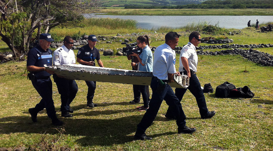 Police carry a piece of debris from an unidentified aircraft found in the coastal area of Saint-Andre de la Reunion, in the east of the French Indian Ocean island of La Reunion, on July 29, 2015. © Yannick Pitou