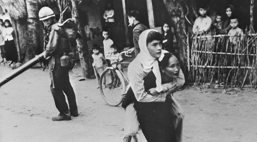 South Vietnam. A Vietnamese woman with her wounded son on her back in a village captured by American Forces. © RIA Novosti
