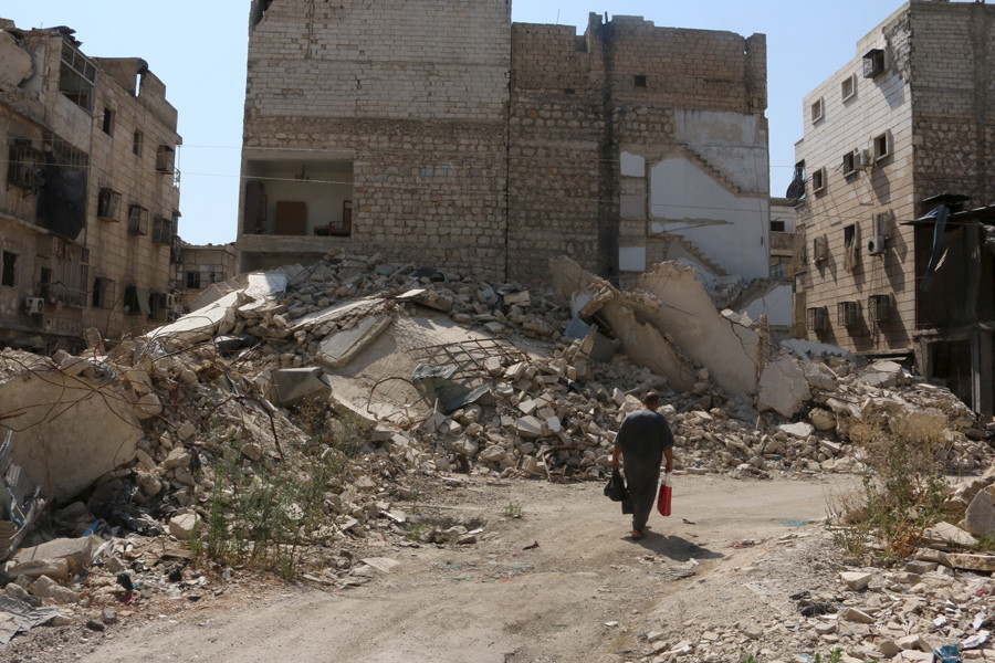 A man walks along a damaged street in the al-Katerji district in Aleppo, Syria © Abdalrhman Ismail