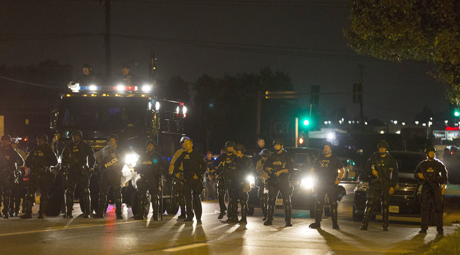 Police officers patrol a street in Ferguson, Missouri August 11, 2014. © Mario Anzuoni
