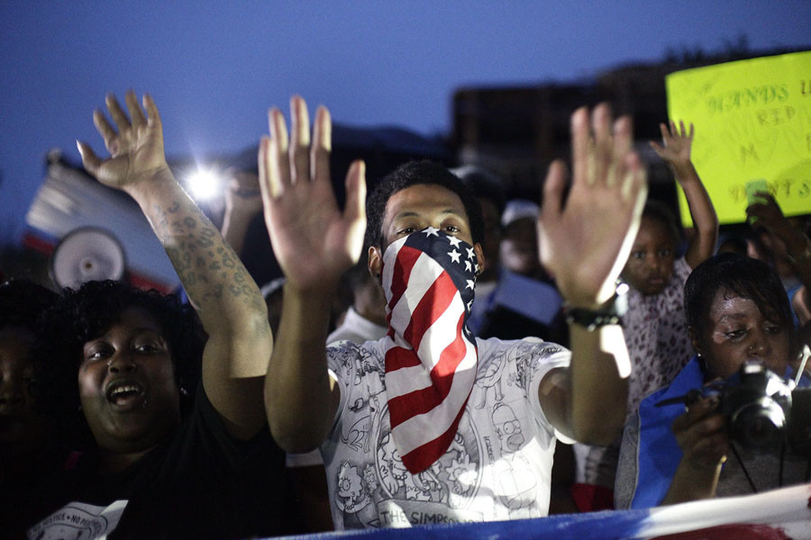 Demonstrators raise their hands as they protest the shooting death of 18-year-old Michael Brown on August 15, 2014 in Ferguson, Missouri. © Joshua Lott