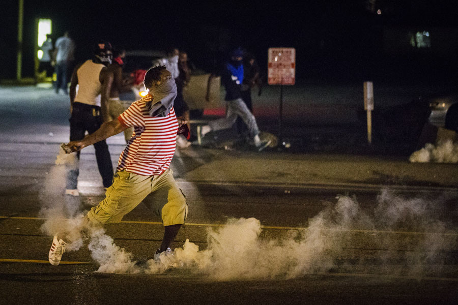 A protester picks up a gas canister to throw back towards the police after tear gas was fired at demonstrators who are continuing to react to the shooting of Michael Brown in Ferguson, Missouri August 17, 2014. © Lucas Jackson