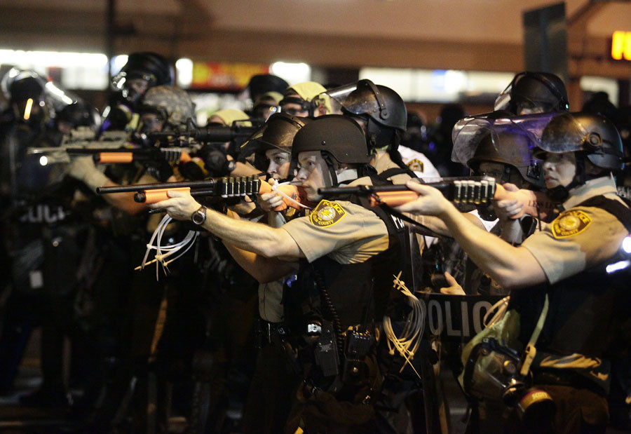 Police officers point their weapons at demonstrators protesting against the shooting death of Michael Brown in Ferguson, Missouri August 18, 2014. © Joshua Lott
