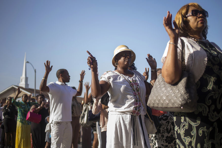 "Attendees hold their hands up while chanting ""Hands up don't shoot,"" as they wait in line to take part in the funeral services for 18-year-old Michael Brown at the Friendly Temple Missionary Baptist Church in St. Louis, Missouri, August 25, 2014. © Adrees Latif"