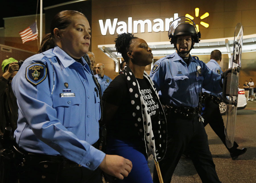 A protester is detained by police officers during a demonstration at a Walmart store in St. Louis, Missouri, October 13, 2014. © Jim Young