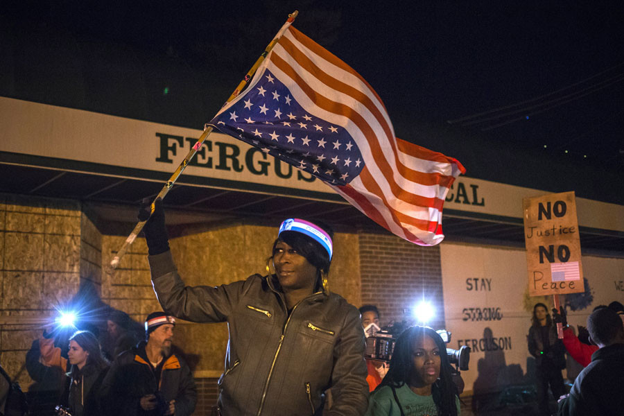 A woman holds an upside-down American flag from a moving vehicle as she takes part in a protest near the Ferguson Police Station in Ferguson, Missouri November 29, 2014. © Adrees Latif