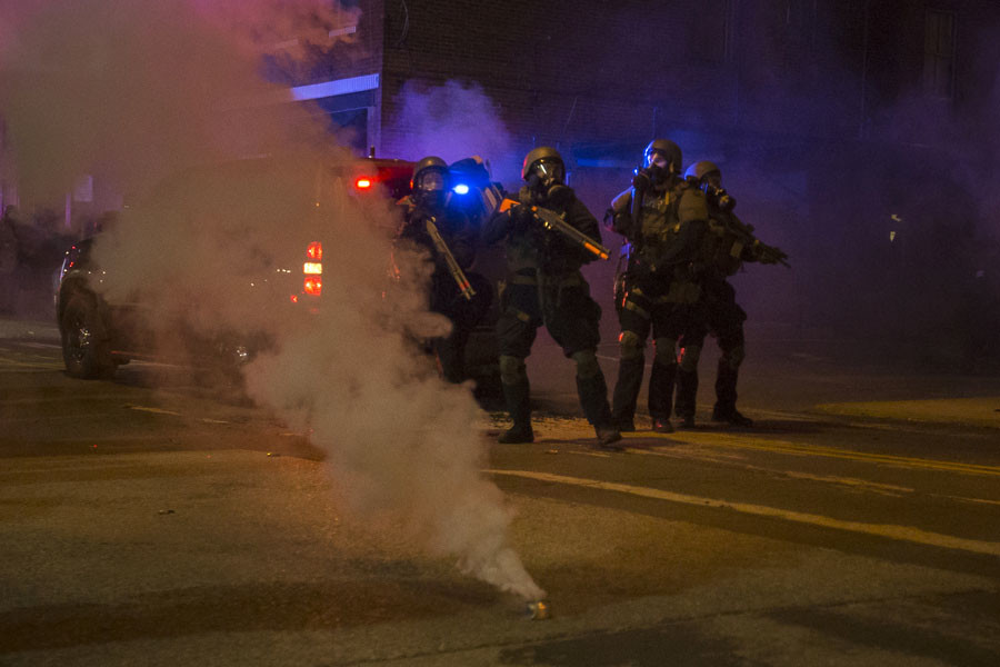 Police in riot gear stand guard after deploying tear gas to disperse protesters in Ferguson, Missouri November 25, 2014. © Adrees Latif