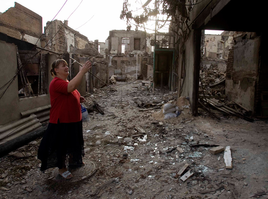 A local woman stands in front of the ruins of her house which was destroyed during the recent conflict in South Ossetia's capital of Tskhinvali August 12, 2008. © Vasily Fedosenko