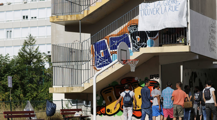 "Migrants walk in the courtyard at the Guillaume-Bude secondary school, near a banner which reads, ""Flee from War, Live on the Streets"" in Paris, France, August 2, 2015. © Stephane Mahe"