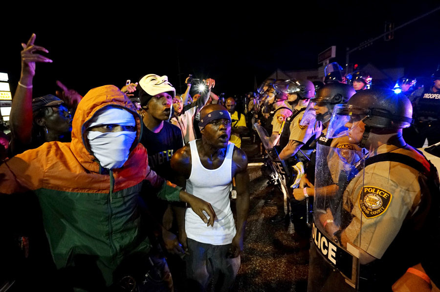 Protesters yell at a police line shortly before shots were fired in a police-officer involved shooting in Ferguson, Missouri August 9, 2015. © Rick Wilking