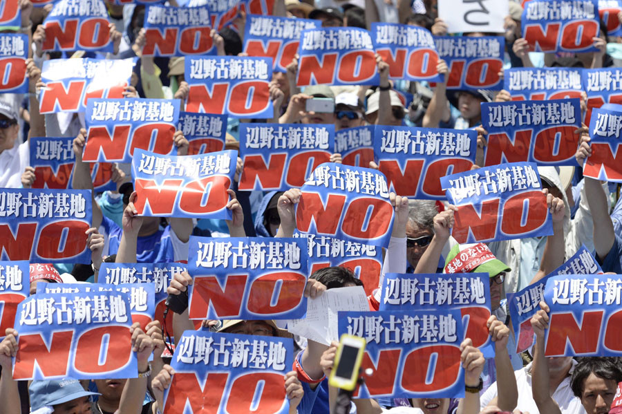 Protesters raise placards during a rally to oppose the transfer of a key U.S. military base within the prefecture, at a baseball stadium in the prefectural capital Naha on Japan's southern island of Okinawa, in this photo taken by Kyodo May 17, 2015. © Kyodo