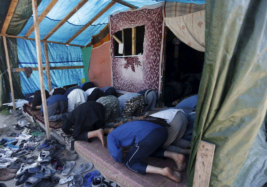 "Migrants pray at a makeshift mosque in ""The New Jungle"" camp in Calais, France, August 7, 2015. © Peter Nicholls"