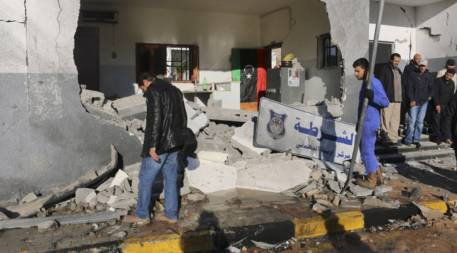 Civilians and security personnel stand at the scene of an explosion at a police station in the Libyan capital Tripoli March 12, 2015. © Hani Amara