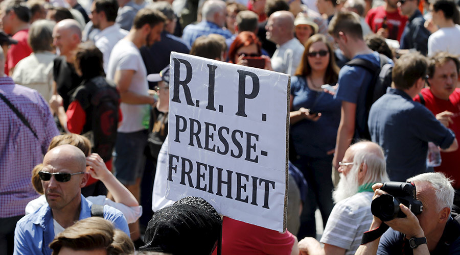 "A demonstrator holds up a placard which reads ""Rest in Peace freedom of press!"" in Berlin, Germany, August 1, 2015 © Fabrizio Bensch"