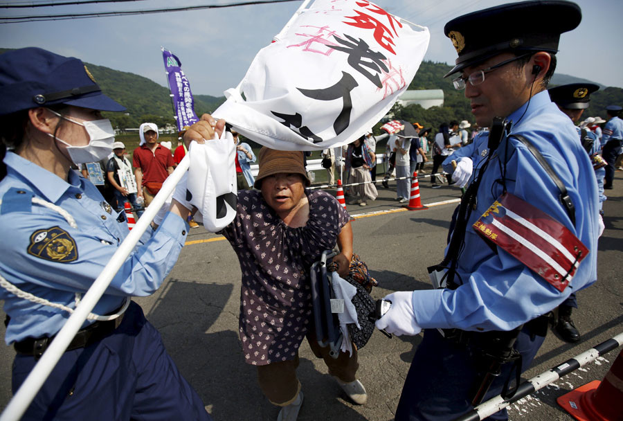 A protester is stopped by police officers during a march against the restarting of the plant in front of an entrance of Kyushu Electric Power's Sendai nuclear power station in Satsumasendai, Kagoshima prefecture, Japan, August 9, 2015. © Issei Kato