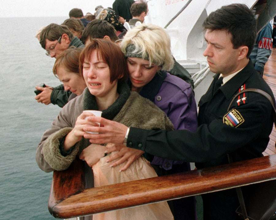 A relative of a sailor who died aboard the Kursk submarine is offered a drink by a naval officer as she is comforted by another mourner during a ceremony held on a ship above the site where the submarine lies in the Barents Sea August 24, 2000. © Reuters