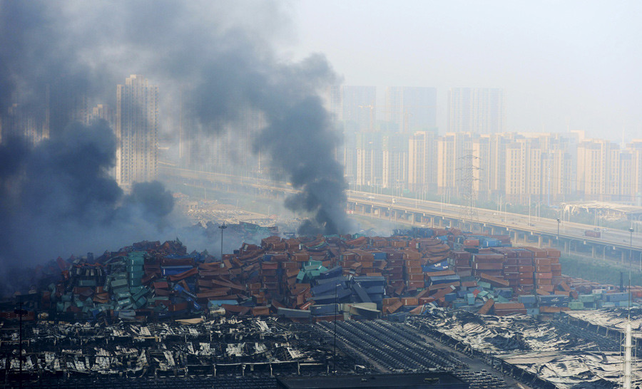 Smoke rises from shipping containers after explosions at Binhai new district in Tianjin, China, August 13, 2015. © Stringer