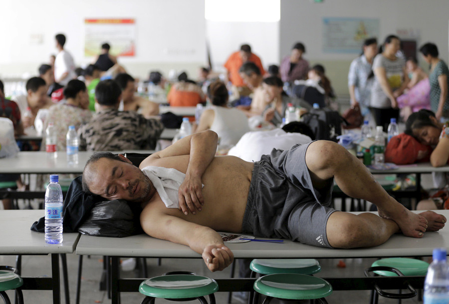 A man rests on a table at a dining hall of a primary school, which has been turned into a shelter for people living nearby, near the site of the explosions at the Binhai new district, Tianjin, August 13, 2015. © Jason Lee