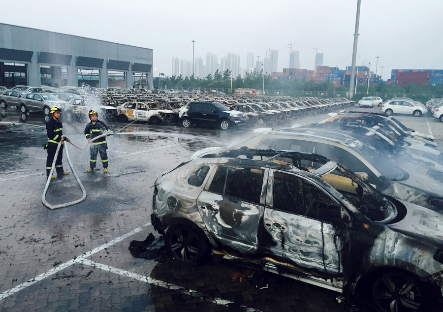 Firefighters work at a parking lot at the site of explosions at the Binhai new district in Tianjin August 13, 2015. © Stringer