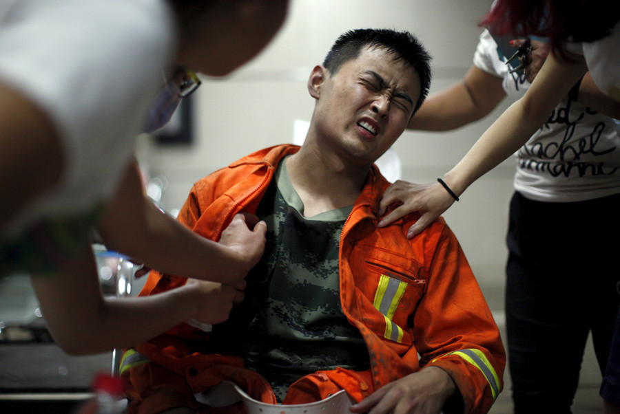 A firefighter reacts as he receives treatment at a hospital after the explosions at the Binhai new district in Tianjin, China, August 13, 2015. © China Daily