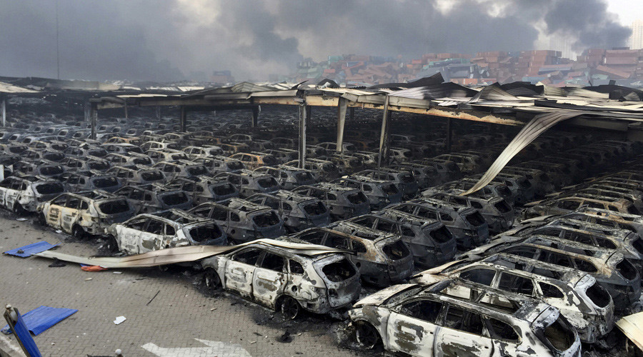 Damaged vehicles are seen as smoke rises from shipping containers after explosions at Binhai new district in Tianjin, China, August 13, 2015. © Stringer