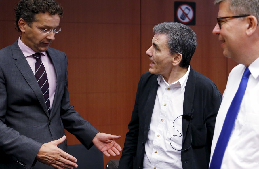 Dutch Finance Minister and Eurogroup President Jeroen Dijsselbloem greets Greek Finance Minister Euclid Tsakalotos (2nd R) at the start of a euro zone finance ministers meeting in Brussels, Belgium, August 14, 2015. © Francois Lenoir