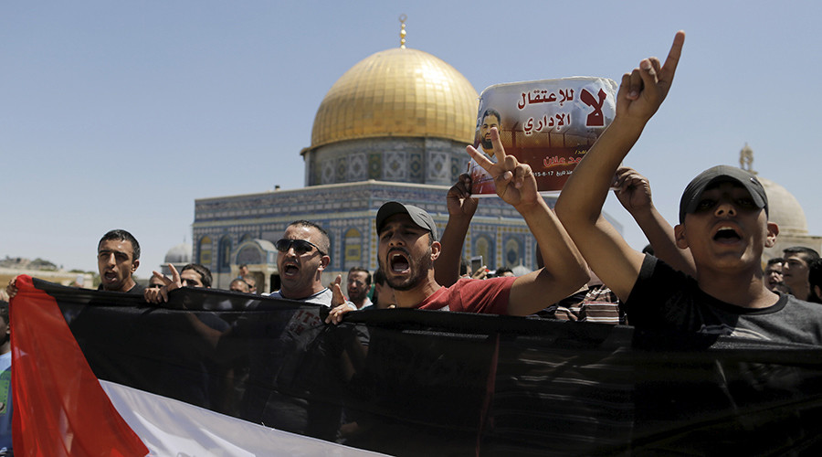 Palestinian protesters hold a placard depicting hunger-striking Palestinian prisoner Mohammed Allan, during a demonstration calling for his release following Friday prayers in Jerusalem's Old City August 14, 2015 © Ammar Awad