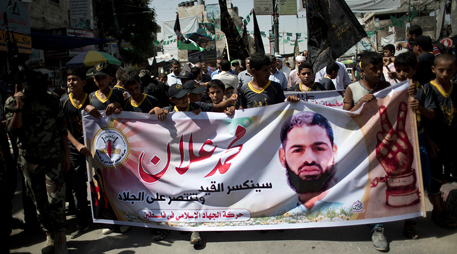 Children hold a placard bearing the portrait of Mohammed Allan during a march organized by the Islamic Jihad at the Rafah refugee camp in the southern Gaza Strip on August 16, 2015 © Said Khatib