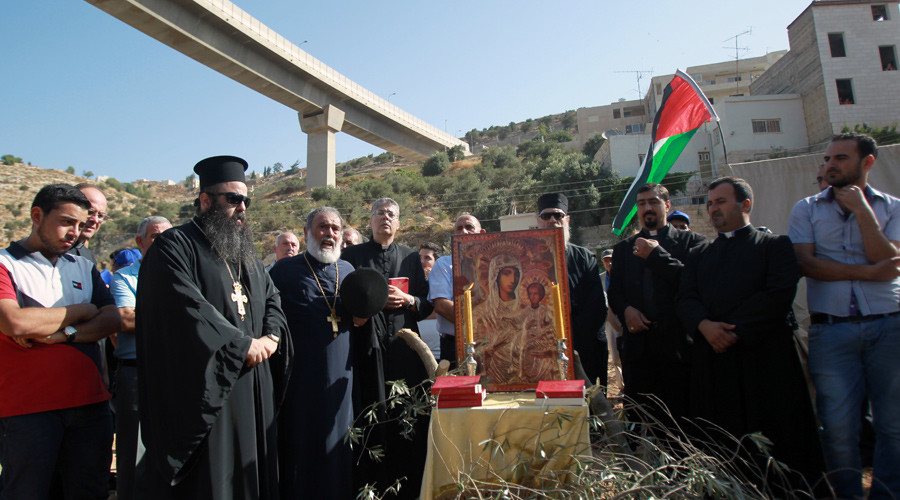 Palestinian Christian worshippers and priests take part in an open-air mass to protest against the building of Israel's controversial barrier in the Cremisan Valley on August 18, 2015 in the West Bank village of Beit Jala. © Musa Al Shaer