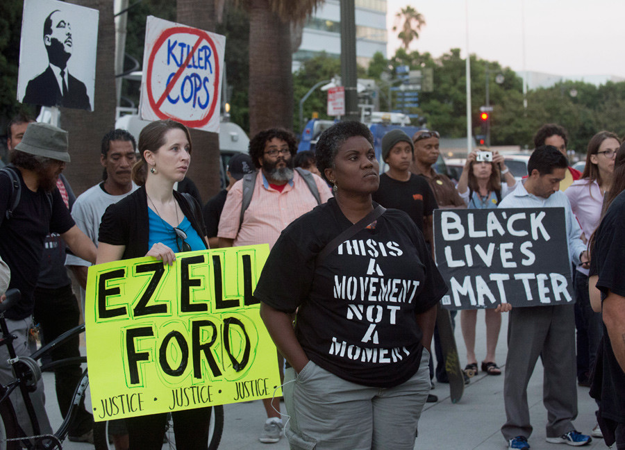 """Protestors carry signs during a demonstration by """"Black Lives Matter"""" in Los Angeles, California August 11, 2015. © Phil McCarten"""