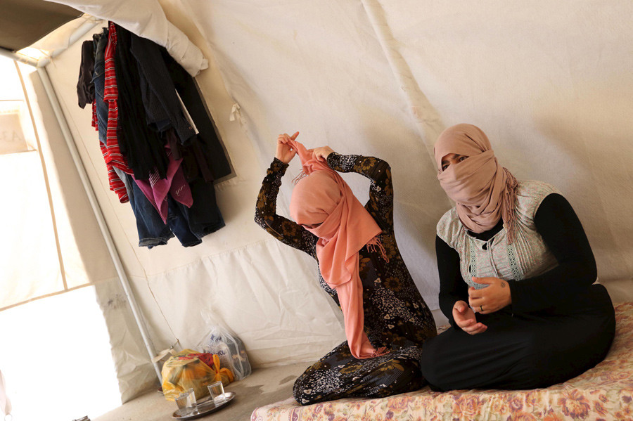 Yazidi sisters, who escaped from captivity by Islamic State (IS) militants, sit in a tent at Sharya refugee camp on the outskirts of Duhok province © Ari Jala