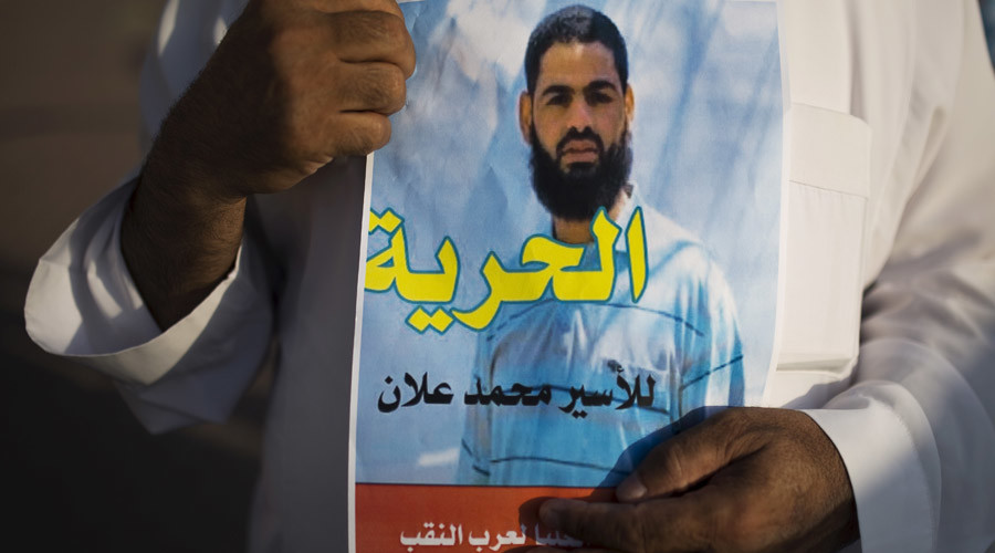 A Bedouin demonstrator holds a sign during a protest in the southern town of Rahat, Israel, in support of Islamic Jihad activist Mohammed Allan, who is in the ninth week of a hunger strike against his detention without trial, August 18, 2015. © Amir Cohen
