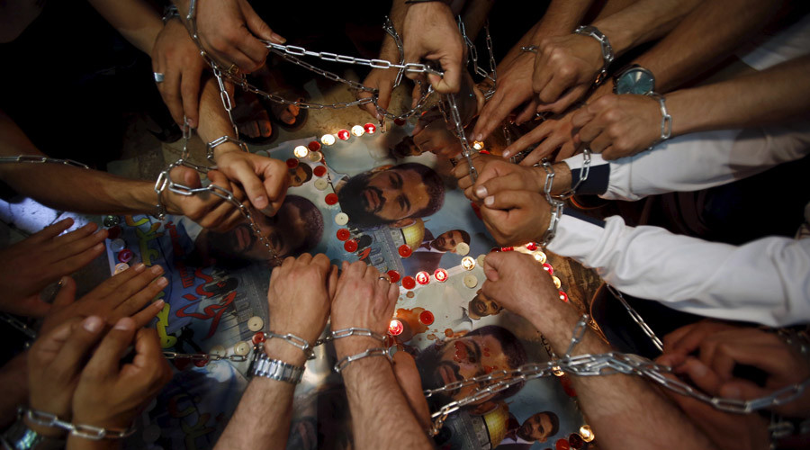 Palestinian lawyers light candles and have their hands chained over posters depicting Palestinian detainee Mohammed Allan during a protest in support of Allan in the West Bank city of Hebron August 19, 2015. © Mussa Qawasma