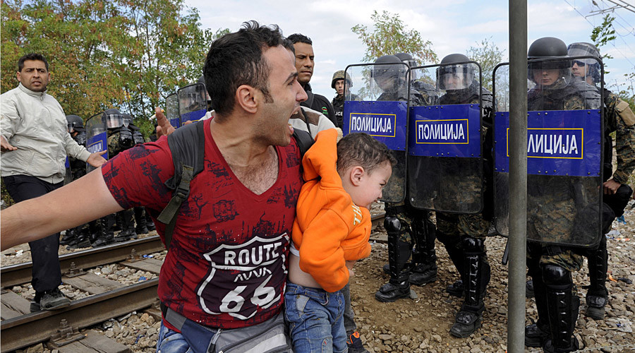 A migrant reacts as he carries a child during clashes with Macedonian police at the Greek-Macedonian border, August 21, 2015. © Alexandros Avramidis