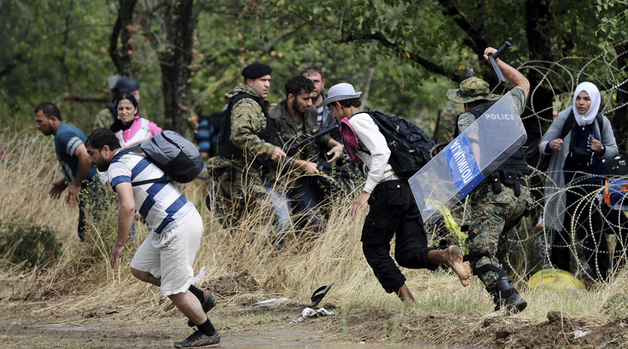A policeman chases migrants who crossed Greece's border into Macedonia near Gevgelija, Macedonia, August 22, 2015. © Ognen Teofilovski