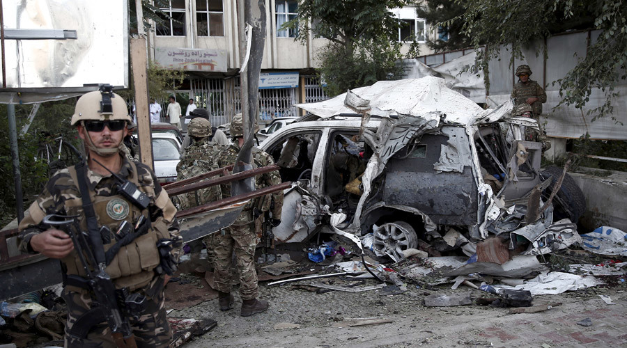 Afghan security personnel (L) keeps watch next to a damaged car belonging to foreigners, after a bomb blast in Kabul, Afghanistan August 22, 2015 © Ahmad Masood