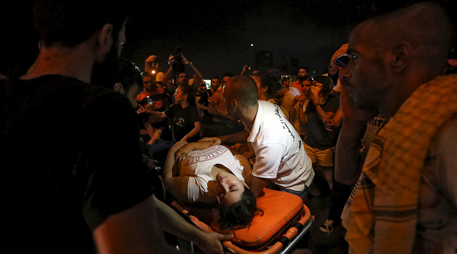 A wounded woman is moved on a stretcher by medics during a protest against corruption and rubbish collection problems near the government palace in Beirut, August 22, 2015 © Hasan Shaaban