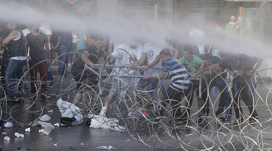 Protesters attempt to remove razor wires as policemen spray water to disperse them during a protest against a rubbish collection problem near the government palace in Beirut, Lebanon © Mohamed Azakir