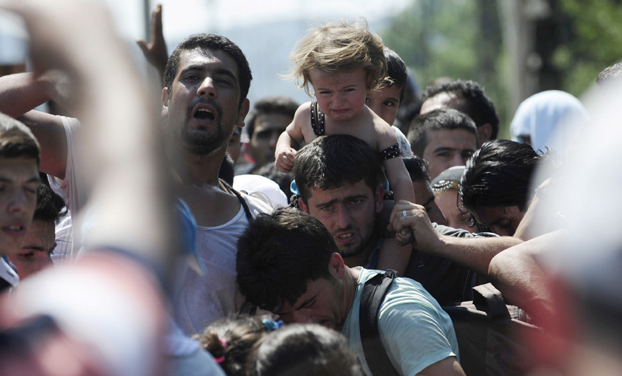 Migrants standing at the Greek side of the border wait to cross into Macedonia, near Gevgelija August 24, 2015. © Ognen Teofilovski
